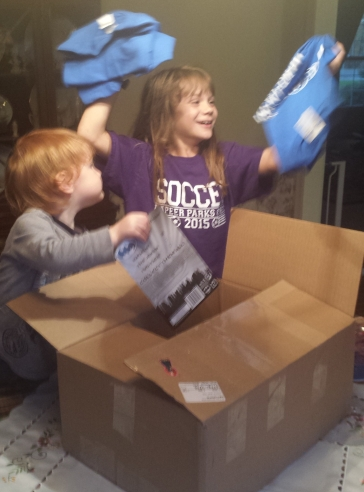 Mercy and Pierson open a box of goodies from MAW, about one week prior to the trip. Mercy is SO excited about our MAW tees!