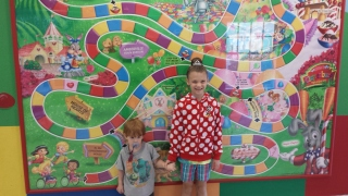 Pierson and Mercy in front of the GKTW Candyland Game Board. (The children were also gifted their own GKTW Candyland game to take home.)