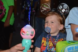 Pierson entranced by his singing bubble wand, a gift from Mickey Mouse.